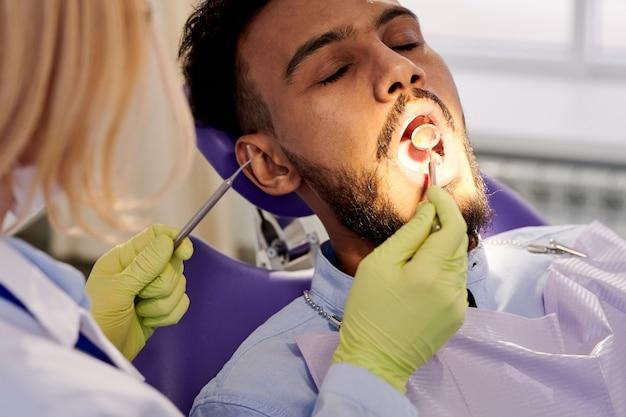 Женский стоматолог, выполняющий экзамен