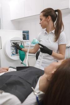 Женский стоматолог готовит ингаляционную седативную маску, чтобы надеть ее пациента