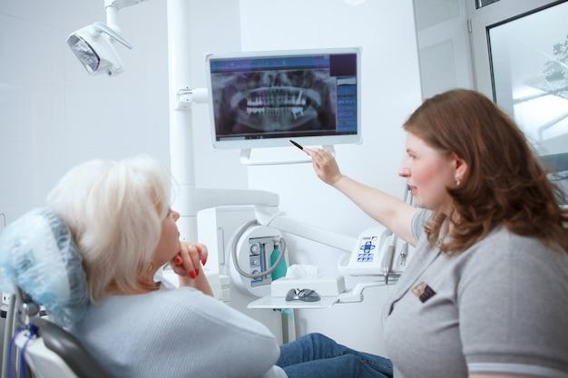 Женский стоматолог показывает стоматологический рентгеновский снимок своему пожилому пациенту