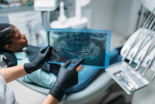 Женский стоматолог показывает проблему на рентгеновском снимке