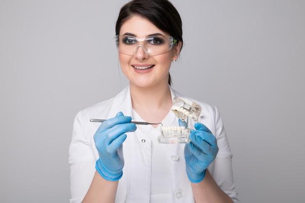 회색 배경에 치과 접시와 여성 치과 의사입니다.