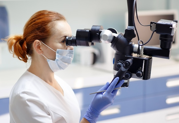 Female dentist with dental tools - microscope, mirror and probe treating patient teeth at dental clinic office, medicine, dentistry and health care concept, dental equipment