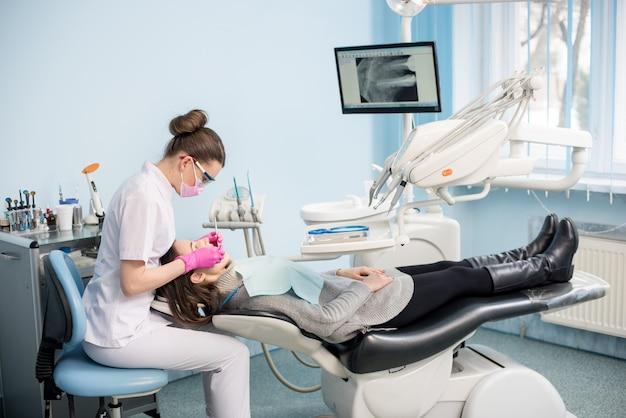Женский дантист с зубоврачебными инструментами - зеркало и зонд обрабатывая терпеливые зубы на офисе стоматологической клиники. концепция медицины, стоматологии и здравоохранения. стоматологическое оборудование