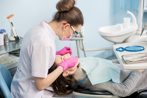 Female dentist with dental tools - mirror and probe treating patient teeth at dental clinic office