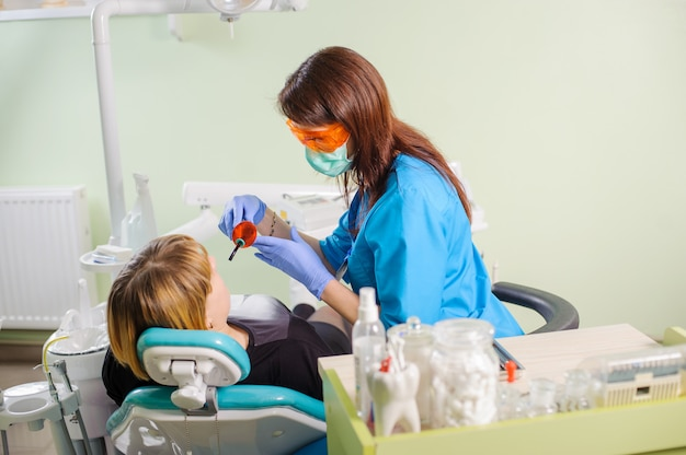 Female dentist with dentist photopolymer lamp