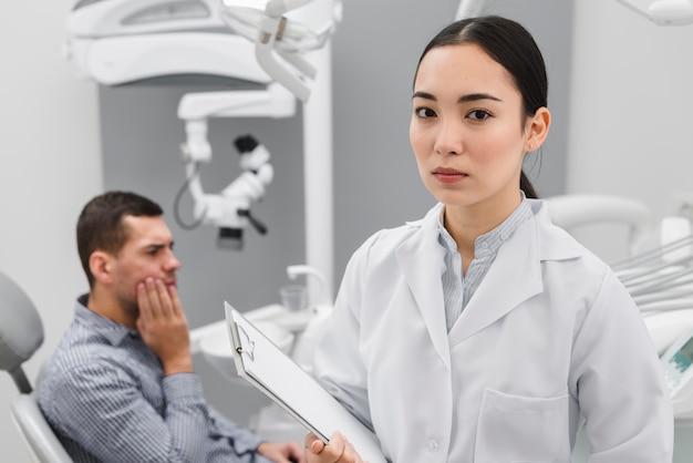 Женский стоматолог с пациентом