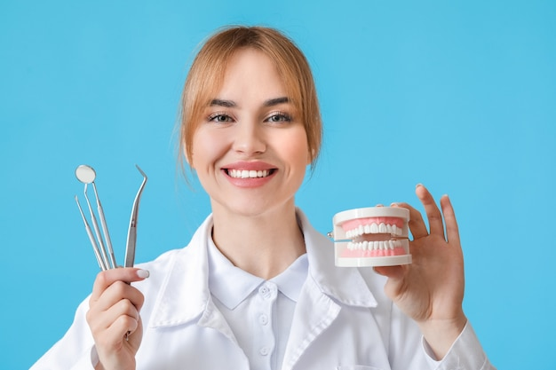 Female dentist with plastic jaw model and tools on color surface