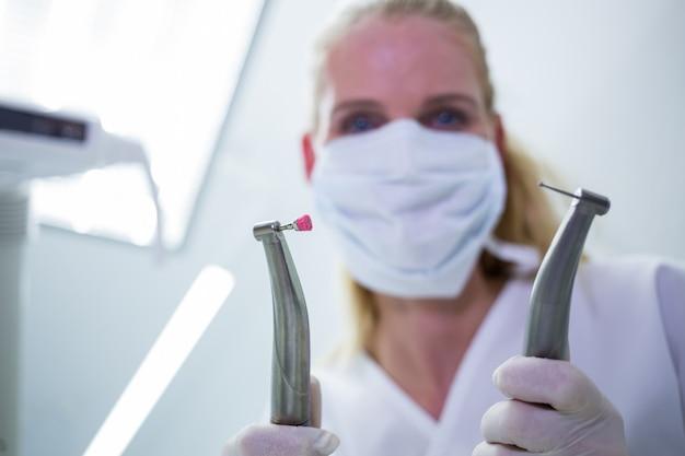 Dentista femminile con la mascherina chirurgica che tiene gli strumenti dentali