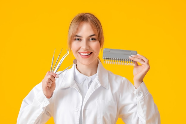 Female dentist with tools and teeth color chart on yellow surface