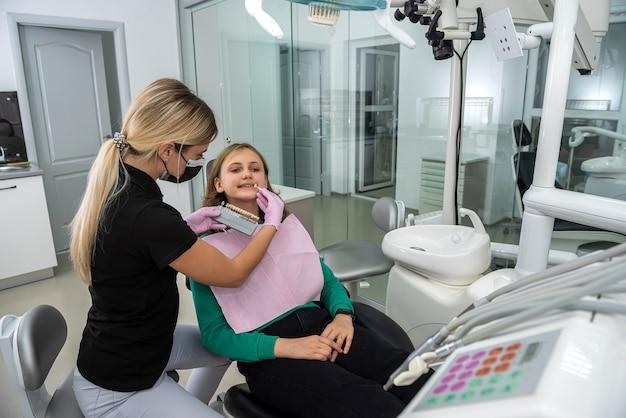 歯の色のサンプルをチェックして色合いを選択する女性歯科医