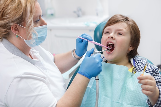 Женский стоматолог работает в своей клинике, лечит зубы молодого мальчика