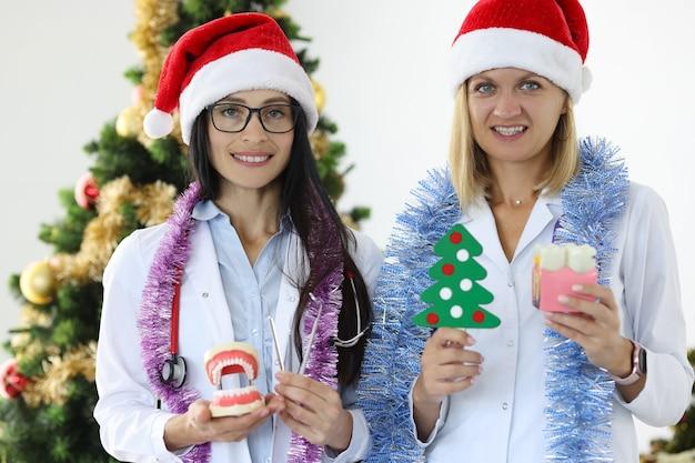 模擬顎とクリスマスツリーを保持しているサンタクロースの帽子をかぶっている女性の歯科医