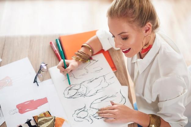 テーブルでスケッチする女性のデザインの専門家