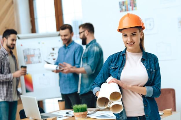 Female designer architect posing with blueprints.