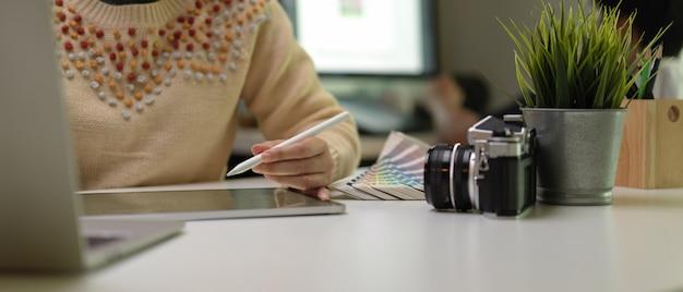 노트북 및 디자이너 용품을 사용하는 동안 디지털 태블릿에 드로잉하는 여성 디자이너