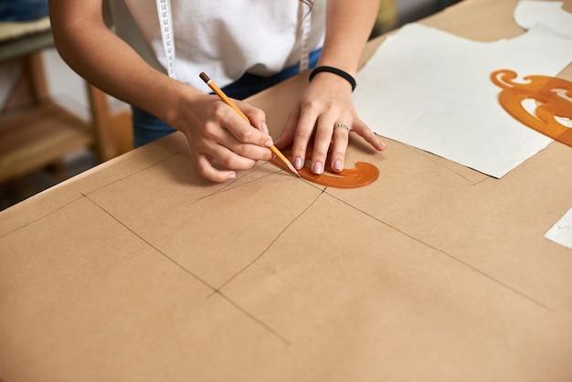 段ボールに線を引く女性デザイナーの手