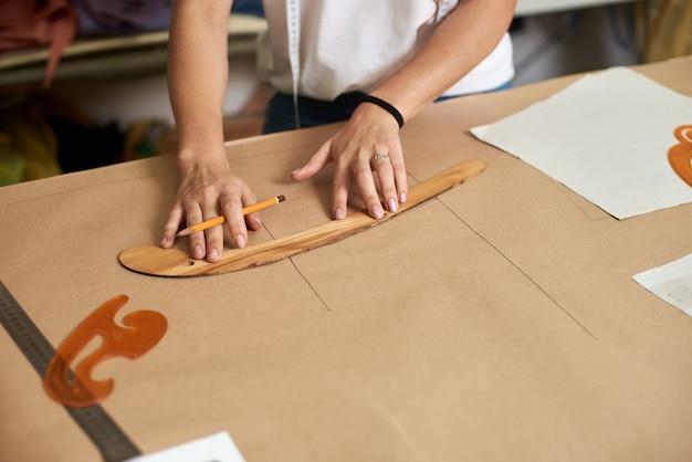 Женский дизайнер вручает рисовать линии на картоне