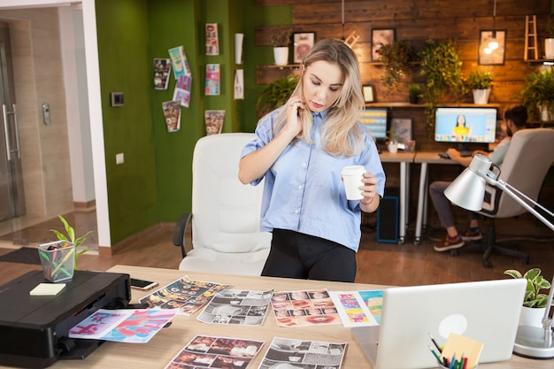 Female designer in her modern office holding a cup of coffee. man retouching a photo in the background.