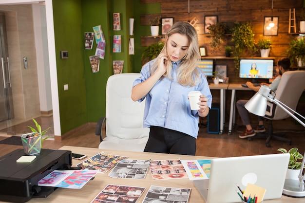 一杯のコーヒーを保持している彼女のモダンなオフィスの女性デザイナー。背景の写真をレタッチする男。