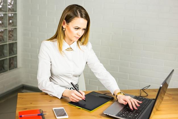 デジタルグラフィックタブレットとラップトップを扱うオフィスの女性デザイナー。机に座って写真レタッチャー。