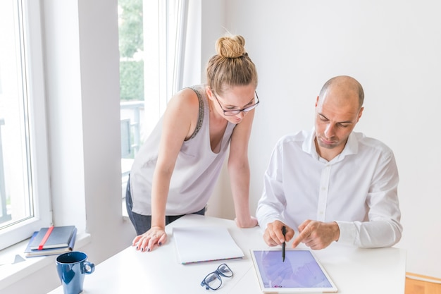 Female designer looking at man showing with stylus on graphic digital tablet at workplace