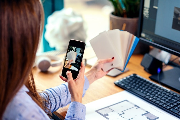 Female designer in office working with colour samples. woman at workplace makes a photo of color palette on smartphone.