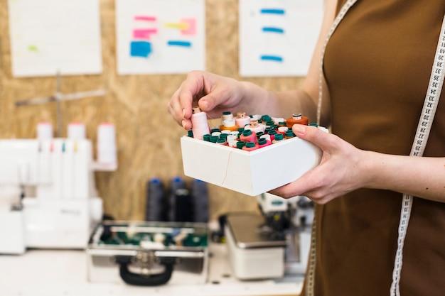 Female designer's hand holding container full of threads