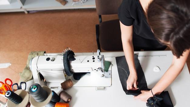パターンで服を縫う女性デザイナー