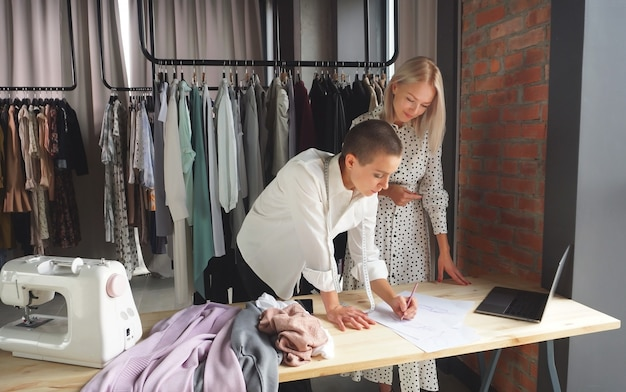 Female designer shows her hand-made clothing sketches to a beautiful client. the concept of fashion design