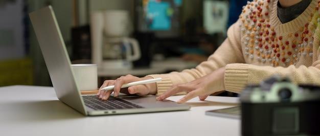 카메라, 태블릿 및 커피 컵 흰색 사무실 책상에 노트북을 사용하는 여성 디자이너