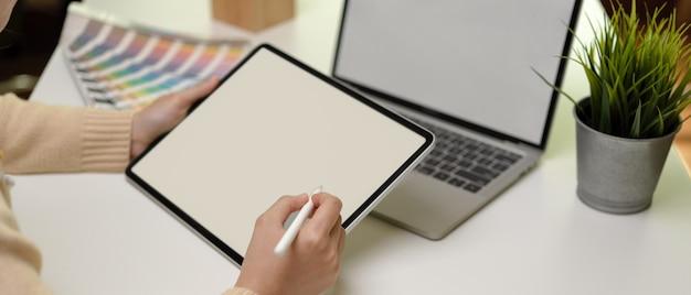 노트북 및 디자이너 용품과 작업 테이블에 앉아있는 동안 태블릿을 사용하는 여성 디자이너