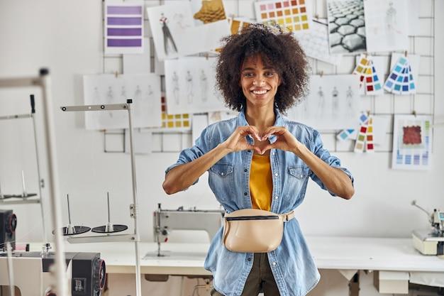 ベルトバッグを持つ女性デザイナーは、現代のミシンの近くに立っている手で心を示しています