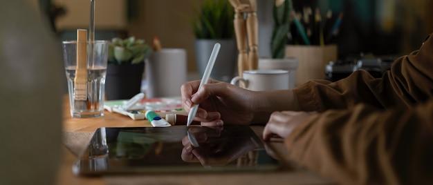 Женский дизайнер работает над цифровым планшетом, сидя на рабочем месте с инструментами рисования и расходных материалов