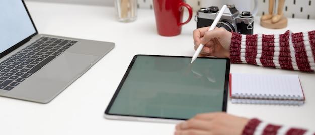 スタイラスが付いているテーブルのモックアップとカメラと用品の白いテーブルの上のノートパソコンのモックアップに取り組んでいる女性デザイナー