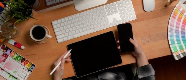 Женский дизайнер работает с цифровыми устройствами на офисном столе с инструментами рисования и расходных материалов