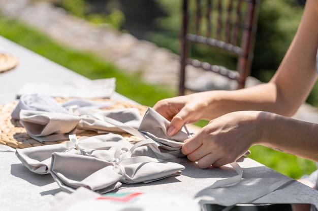 Женщины-дизайнеры украшают место проведения свадебной церемонии под открытым небом.