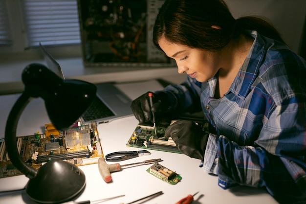Female at desk repairing