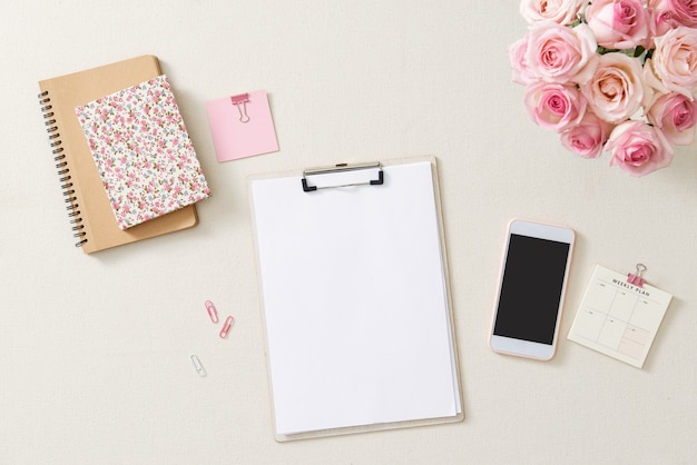 Female desk with pink roses bouquet, pink diary on white. flat lay. top view feminine