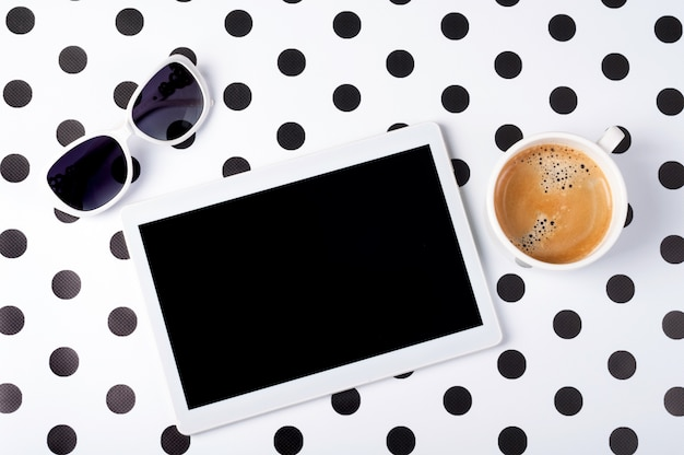 Female desk with tablet, coffee cup, sunglasses on creative background top view