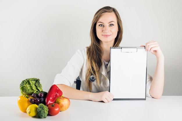 Dietista femminile che tiene appunti in bianco
