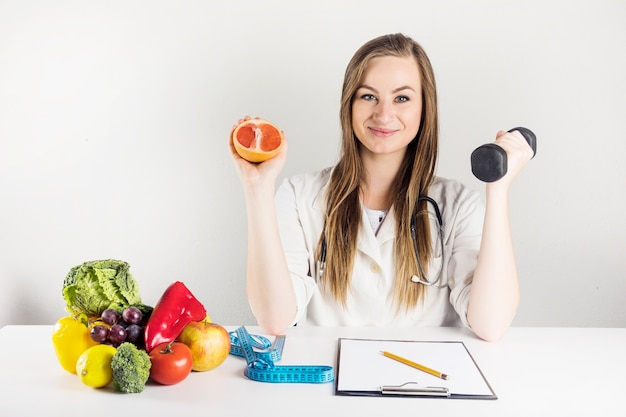 Female dietician holding grapefruit and dumbbell in clinic
