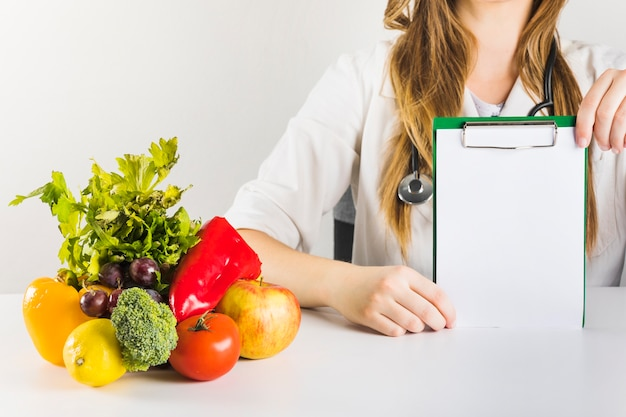 Female dietician's hand holding blank clipboard with healthy food on desk