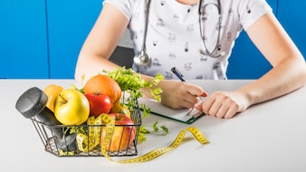 Female dietician's hand near healthy fruits and dumbbells in tray