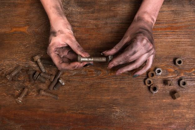 나무 배경에 나사 너트와 볼트를 들고 여성 더러운 손. 더러운 직업은 현대 여성에게 문제가 아닙니다