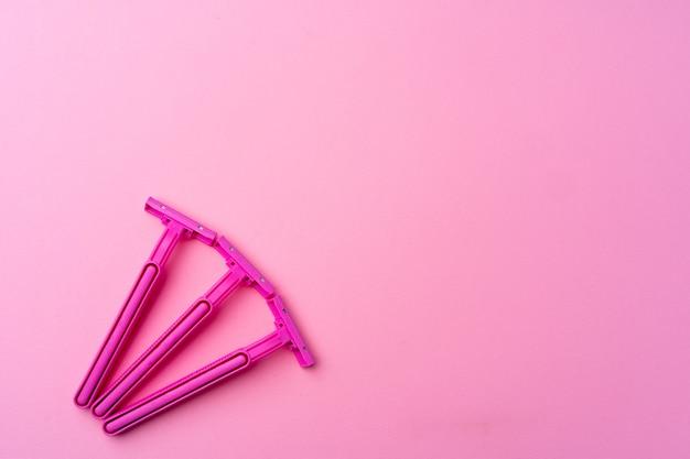 분홍색 배경 평면도에 여성 일회용 면도기, 복사 공간