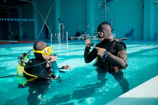 스쿠버 장비를 입은 여성 다이버와 남성 다이브마스터, 다이빙 학교 수업. 사람들에게 수중 수영을 가르치고, 배경에 실내 수영장 내부