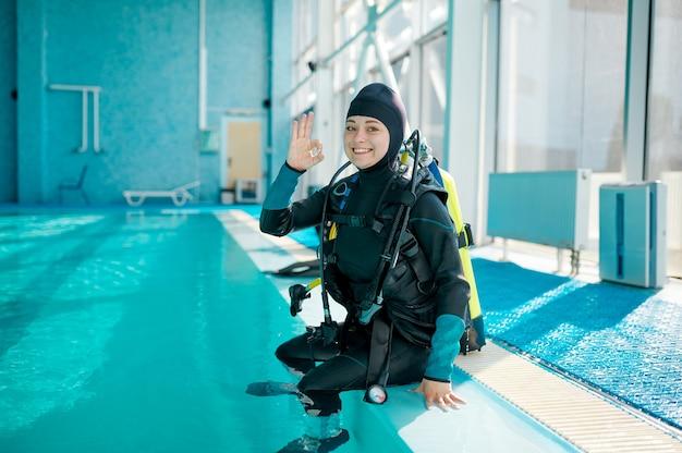 Женщина-водолаз в костюме с аквалангом сидит у бассейна, школа подводного плавания. обучение людей плаванию под водой, интерьер крытого бассейна на заднем плане