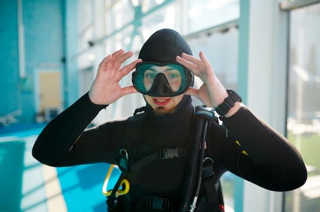 Женщина-дайвер в костюме с аквалангом сидит у бассейна