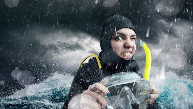나쁜 날씨에 바다에서 잠수복과 다이빙 장비에 여성 다이버. frogman 해변, 수중 스포츠