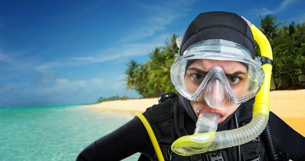 ウェットスーツとダイビングのギア、背景にオーシャンショアの女性ダイバー。マスクとビーチ、水中スポーツのスキューバのフロッグマン